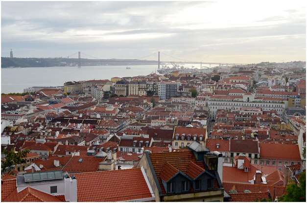 A wonderful view of the Baixa, with the River Tagus in the distance. The bridge is the Ponte 25 de Abril (25th of April Bridge to commemorate the1974 revolution which overthrew the ultra-right wing Salazar government). Built by the same company that built the San Francisco-Oakland Bay bridge, it wascompleted in 1966. The upper deck carries six car lanes and the lower deck two railway tracks (added in 1999). At 2 277m it's the 23rd longest suspension bridge in the world. Also visible on the far left is the statue of Christ the King, a 110m tall structure completed in 1959.